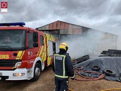 Bomberos trabajan en la extinción de un incendio en una nave agrícola de Morella (Castellón)