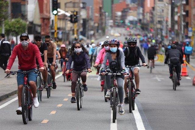 Personas con mascarilla van en bicicleta por una calle de Bogotá, Colombia.