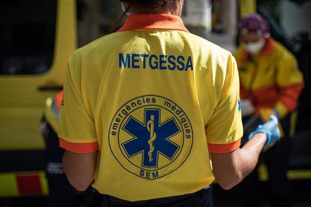 Dos técnicos del Sistema de Emergencias Médicas (SEM) de la Generalitat de Cataluña mueven una camilla junto a una ambulancia durante un servicio y limpieza de EPIs, en Barcelona/Catalunya (España) a 19 de abril de 2020.