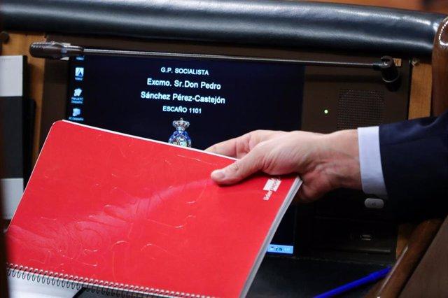 El presidente del Gobierno, Pedro Sánchez, deja su cuaderno de notas en la mesa de su escaño tras una intervención ante el Pleno del Congreso