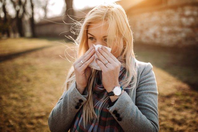 Foto de archivo. Mujer se suena la nariz, catarro, alergía.