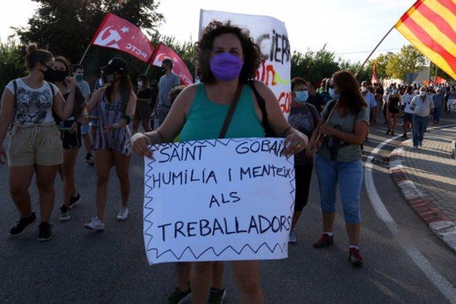 Pla obert d'una manifestant amb un cartell reivindicatiu en la protesta dels treballadors de la fàbrica de Saint-Gobain per denunciar el tancament de la divisió Glass. Imatge del 20 de setembre del 2020 (Horitzontal).