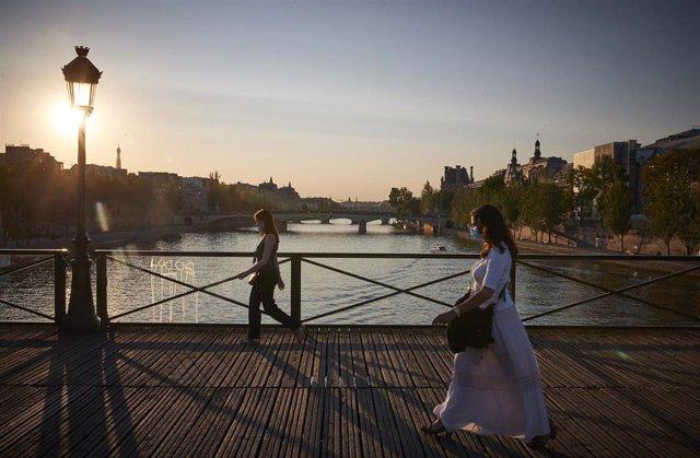 Personas con mascarilla sobre un puente del río Sena en París