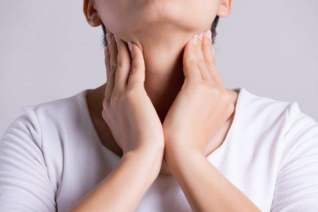 Mujer joven tocando su cuello. Ganglios, tiroides, garganta.