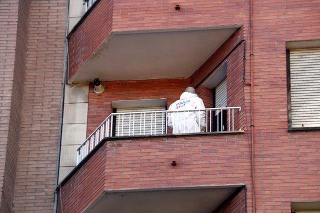 Un efectiu de la policia científica dels Mossos al balcó del pis de l'avinguda de les Garrigues de Lleida on ha tingut lloc l'homicidi. Imatge del 19 de setembre de 2020. (Vertical)