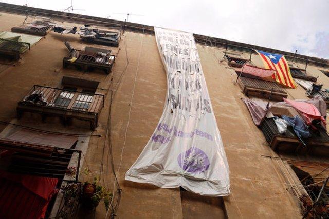 Pla contrapicat de l'edifici situat al número 6 del carrer Sant Bartomeu, al Raval, amb una pancarta penjant. Imatge del 21/09/2020 (horitzontal)