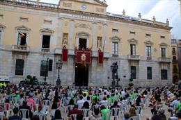 Pla general de la plaça de la Font de Tarragona durant el pregó de Santa Tecla, amb desenes de persones assegudes per la covid-19. Imatge del 21 de setembre del 2020. (Vertical)