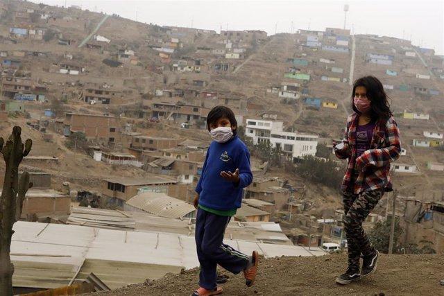 Dos niños con mascarilla caminan por la barriada de Villa Maria del Triunfo, Lima, en medio de la pandemia del coronavirus.