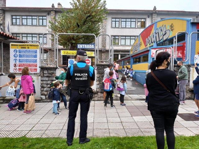Un policía local controla el acceso al Colegio Público La Gesta de Oviedo en el primer día de clase
