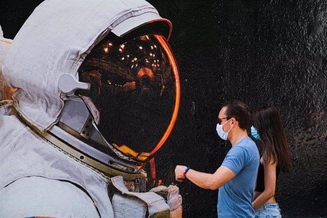 Dos personas con mascarilla pasan ante un mural de un astronauta en Hong Kong