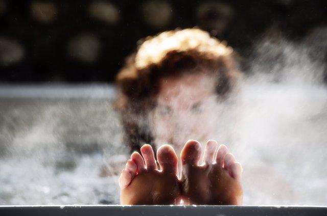 Mujer dándose un baño caliente.