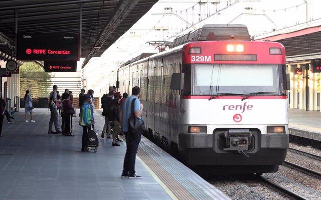 Varios pasajeros se disponen a coger un tren en el andén de la estación de tren de Renfe de Alcorcón (Madrid)