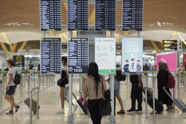 Pasajeros cerca de páneles informativos en la terminal T4 del aeropuerto Adolfo Suárez Madrid-Barajas, en Madrid (España)