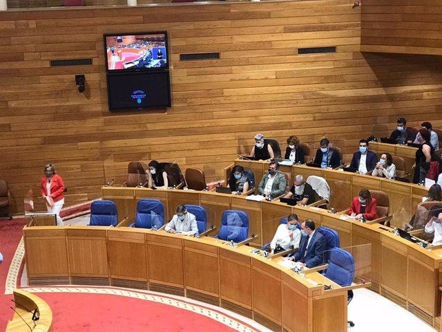 Montse Prado (BNG) camina hacia la tribuna de intervenciones mientras el conselleiro de Sanidade, Julio García Comesaña, habla con la titular de Politica Social, Fabiola García, tras su comparecencia.
