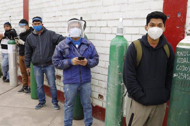 Un grupo de personas hace cola para poder recargar sus bombonas de oxígeno.