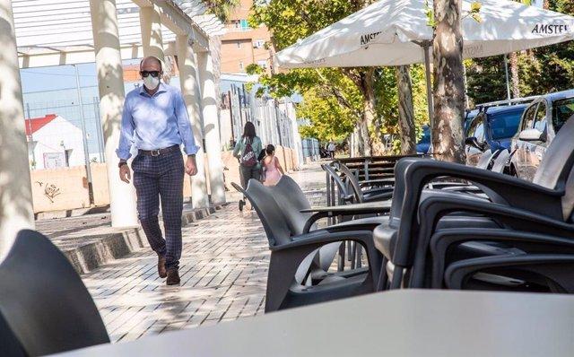 Un hombre camina junto a la terraza de un bar