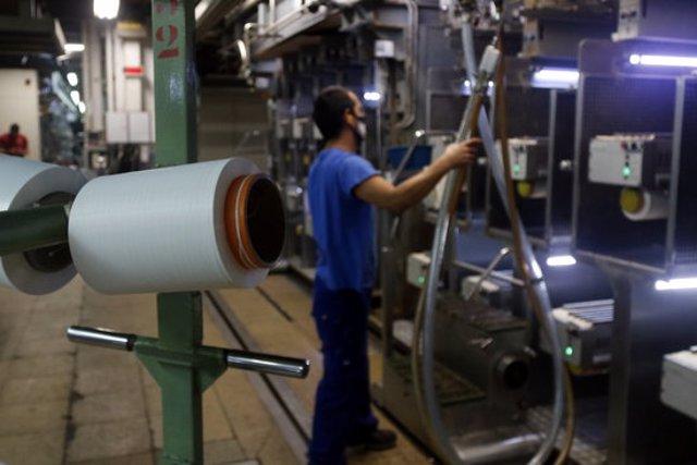 En primer terme, una bobina de fil Meryl; al fons, un operari amb les màquines que el produeixen, aquest 23 de setembre del 2020 a la factoria Nylstar de Blanes (Horitzontal)