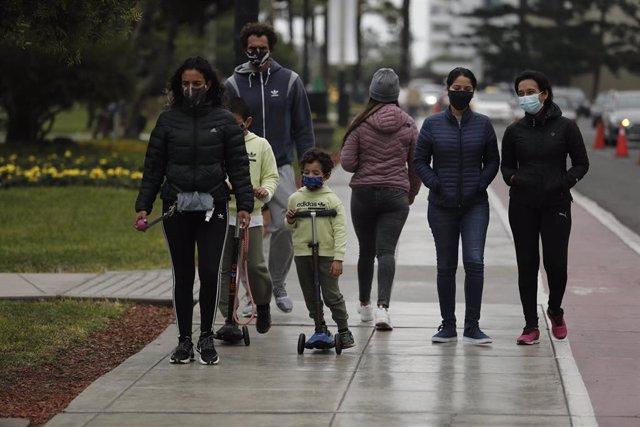 Un grupo de personas pasean por las calles de Lima aprovechando la flexibilización de las medidas de confinamientos levantadas por el Gobierno de Perú.