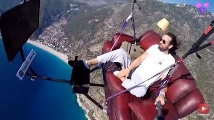 Un hombre vuela en parapente sentado cómodamente en un sofá mientras ve la tele