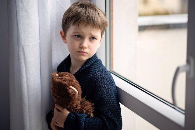 Niño está abrazando a su osito de peluche. De pie junto a la ventana. Día lluvioso. Concepto de soledad y espera