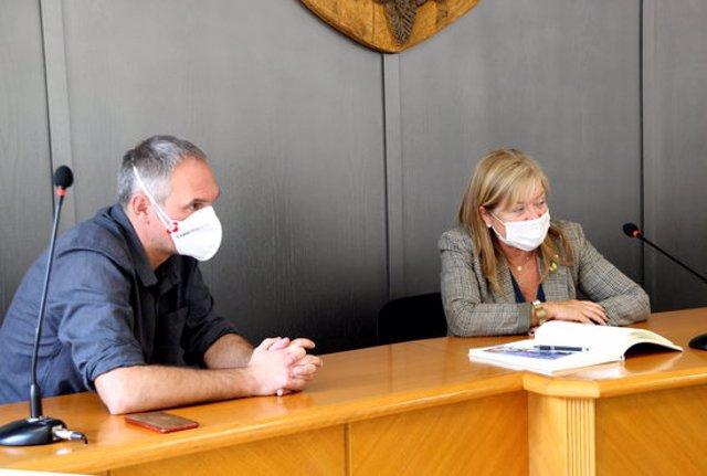 Pla mig de la consellera de Cultura, Àngels Ponsa, a l'Ajuntament de Sort signant el llibre d'honor, acompanyada de l'alcalde de la localitat, Raimon Monterde. Imatge del 24 de setembre del 2020. (Horitzontal)