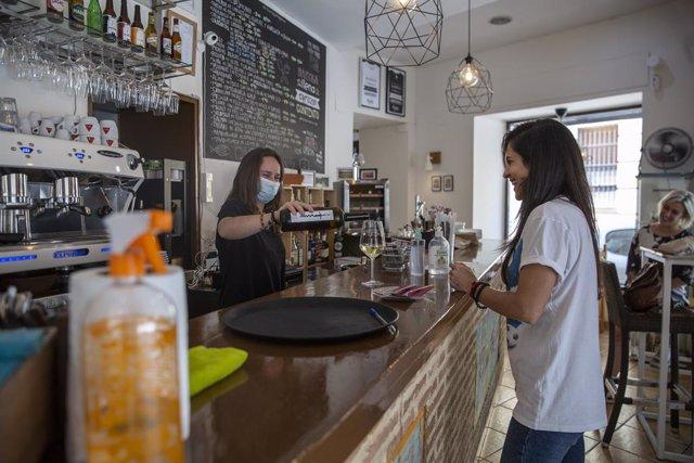 Una camarera sirve una copa de vino a una clienta