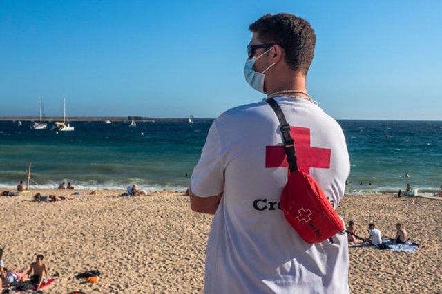 Pla mig d'un socorrista de la Creu Roja vigilant la platja de Palamós en una imatge d'arxiu.