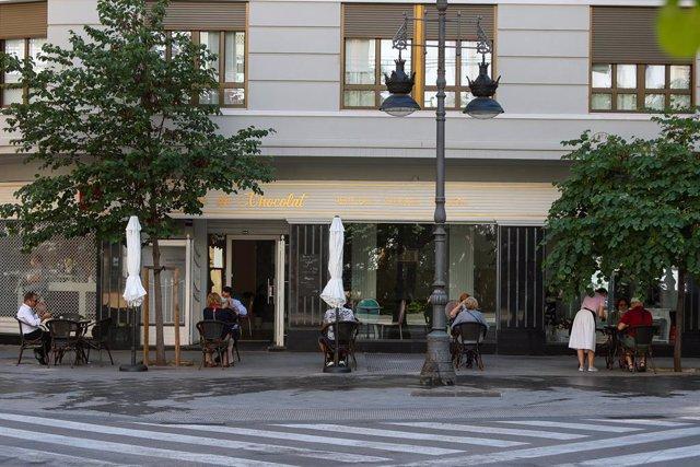 Diverses persones gaudixen en una terrassa d'un bar