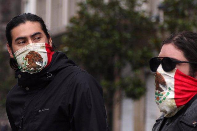 Dos personas se cubren la boca con sendos pañuelos con la bandera mexicana.