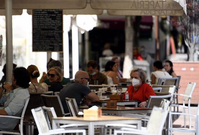 Varias personas disfrutan en una terraza de un bar el día en el que entra en vigor en la Comunidad de Madrid la ampliación del uso obligatorio de la mascarilla