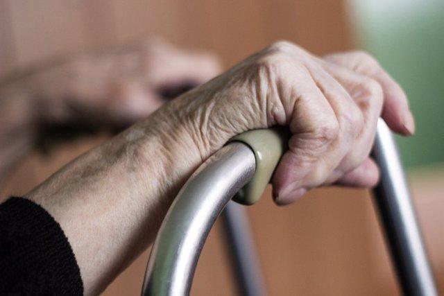 Elderly hands on a walker