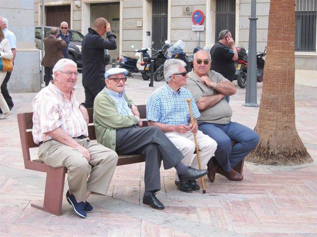 Imagen de un grupo de jubilados sentados en un banco.