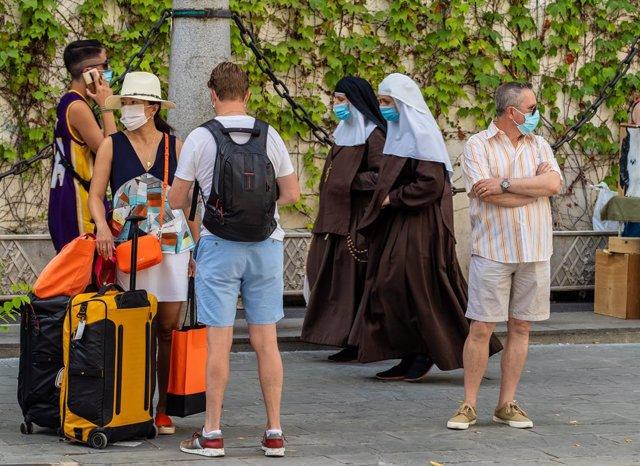 Unos turistas esperan el autobús mientras una pareja de monjas de la Orden de Santa Ángela de la Cruz  pasan por detrás con mascarillas en Sevilla