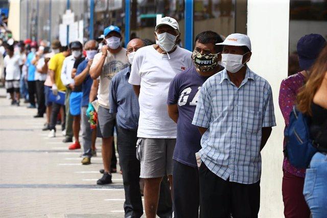 Un grupo de personas hace cola en una sucursal bancaria en un distrito de Lima para recibir el subsidio de 380 soles (90 euros) que otorga el Gobierno de Perú durante la crisis de la pandemia.