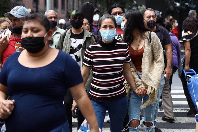 Varias personas pasean por las calles de México con mascarilla por el coronavirus.