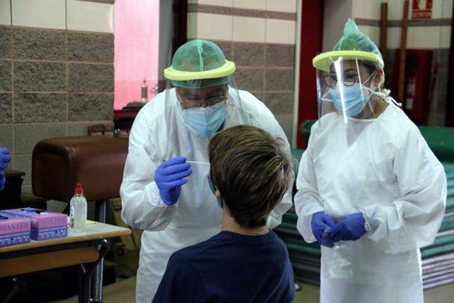 Pla mitjà d'un dels equips mòbils extraient mostres per a PCR a l'escola Bell-lloc de Girona, el 24 de setembre del 2020 (horitzontal)