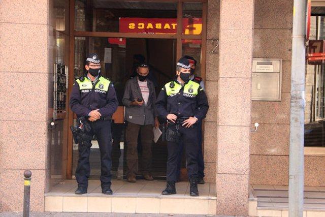 Pla mitjà d'agents de la policia de Girona i dels Mossos a les portes de l'edifici on han trobat la dona aquest 26 de setembre del 2020. (Horitzontal)