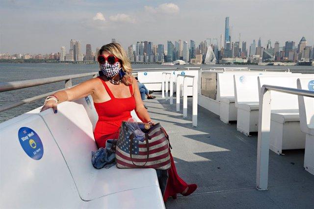 Mujer con mascarilla en un barco turístico en Nueva York durante la pandemia de