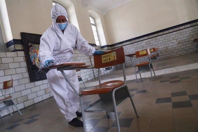 Una trabajadora desinfecta un pupitre en Bogotá por el coronavirus.