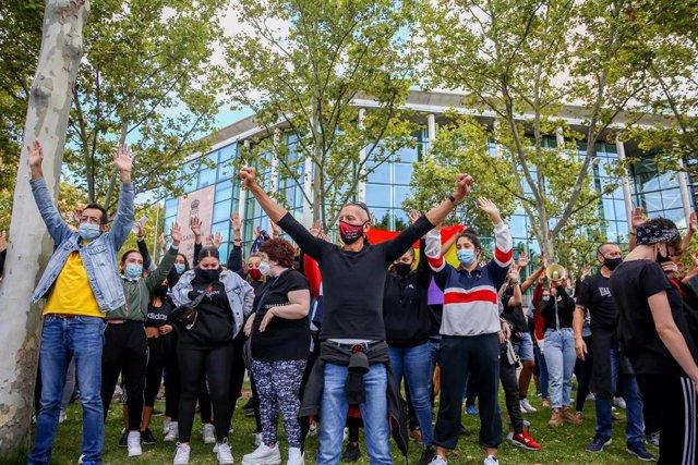 Varias personas levantan las manos durante una concentración bajo el nombre 'Más Sanidad, Menos Policía' frente a la Asamblea de Madrid en el barrio madrileño de Vallecas, en Madrid (España) a 27 de septiembre de 2020.
