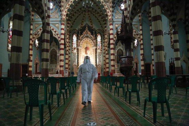 Un hombre ataviado con un  traje de protección camina por una iglesia de Bogotá, después de que en las últimas semanas se reabrieran los lugares de culto con ciertas restricciones a causa de la pandemia.