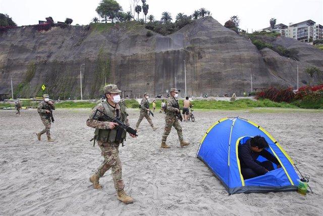 Un grupo de  soldados del ejército de Perú pide a los bañistas de las playas de la Costa Verde, en Lima, que abandonen  el lugar tras decretarse los cierres por la pandemia del coronavirus.