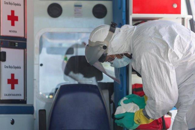 Un bombero limpia una ambulancia de Cruz Roja utilizada para trasladar enfermos de coronavirus, foto de archivo