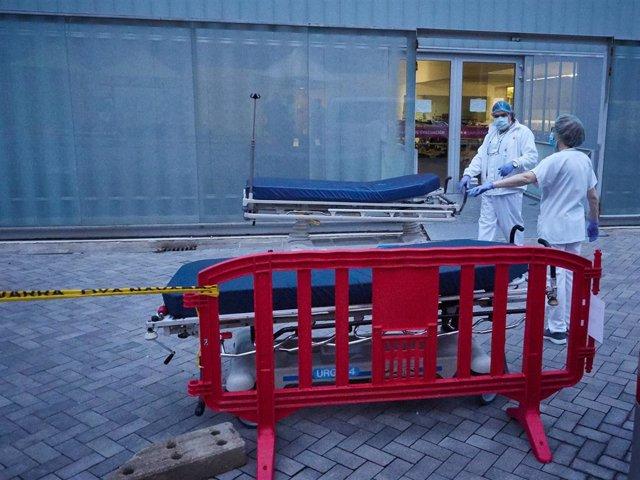 Personal sanitario del Hospital de Navarra traslada una camilla desinfectada en el Servicio de Urgencias