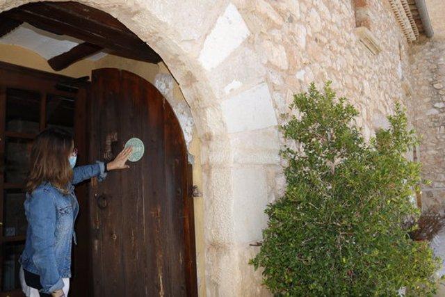 Pla tancat d'una responsable de Turisme de Montblanc, posant un distintiu de qualitat en un allotjament rural de Prenafeta. Imatge del 28 de setembre del 2020. (Horitzontal)