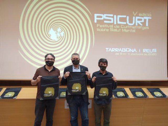 Pla americà de l'alcalde de Tarragona, Pau Ricomà, sostenint el cartell de la cinquena edició del Psicurt entre el director cinematogràfic del festival, Josep Varo (esquerra), i el coordinador, Jaume Descarrega (dreta), el 28/09/20. (Horitzontal)