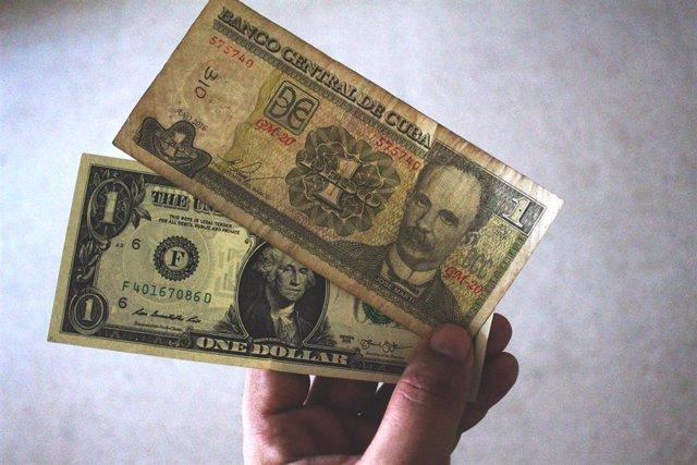 Un hombre sostiene billetes de peso y de dólar