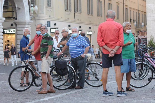 Hombres con mascarilla en una calle en Italia
