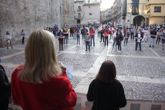 """Pla obert on es veuen desenes de manifestants concentrats davant l'Ajuntament de la Seu d'Urgell amb pancartes de """"Llibertat presos polítics"""" i la persona que llegeix el manifest, d'esquena, en primer terme. Imatge del 28 de setembre de 2020 (Horitzontal)"""