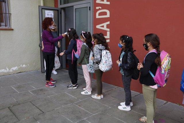 Pla general d'alumnes de l'escola de Manlleu fent cua per prendre'ls la temperatura el 24 de setembre del 2020. (horitzontal)